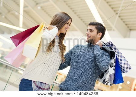 Sale technology and people concept - happy young couple with shopping bags.Image taken inside a shopping mall.