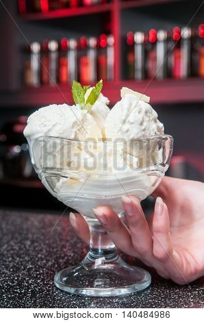glass of ice-cream stands on the bar