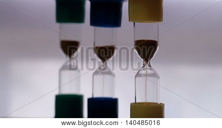 Sand pours in colored sand glasses studio isolated