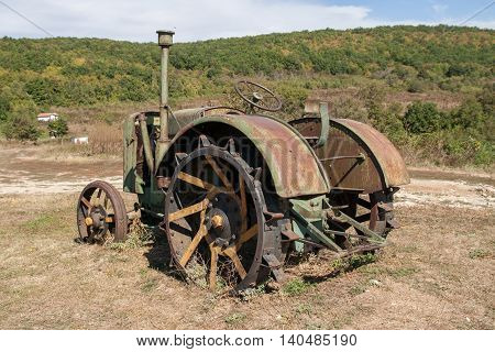 old rusty tractor in a field, abandoned