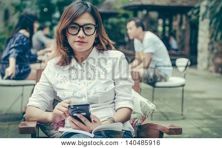 Asian woman taking notes on the phone with the intention.
