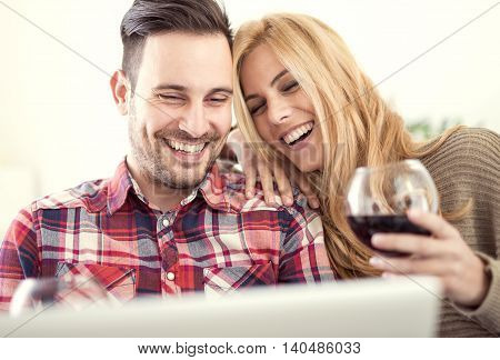 Close up of a young couple enjoying wine at home.They are sitting close to each other and drinking red wine.Love concept.