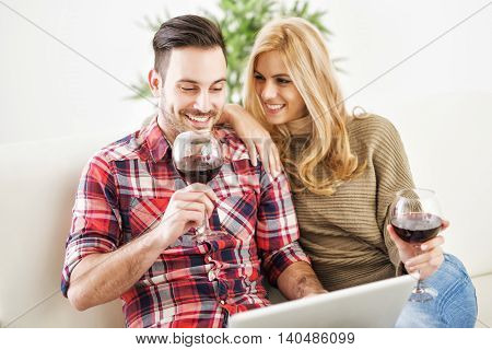 Close up of a young couple enjoying wine at home.They are sitting close to each other and drinking red wine.Love.