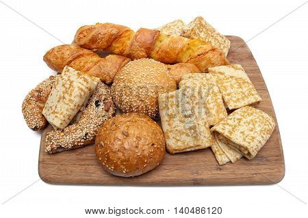 pancakes and baked goods on a cutting board. white background - horizontal photo.