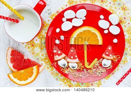Funny idea for baby food - orange and grapefruit slices with marshmallow for dessert or snack in the form of a picture on a plate. Autumn mood food