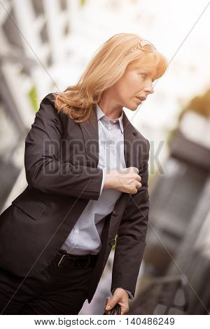 Businesswoman in the city.She is standing in front of an office building.