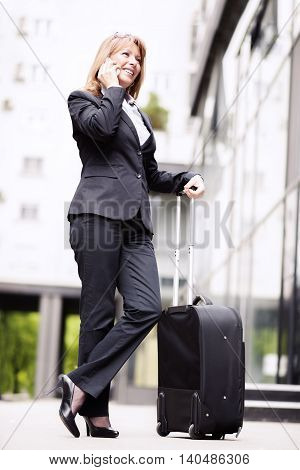 Businesswoman traveling.Front view of a traveler woman walking and using a smart phone in an airport.