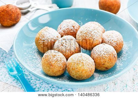 Donuts with powdered sugar in blue bowl selective focus