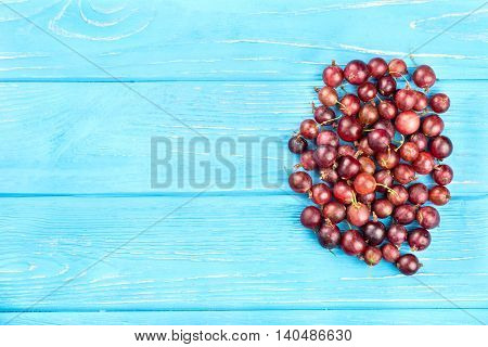 Small handful of red gooseberries on a blank wooden background top view