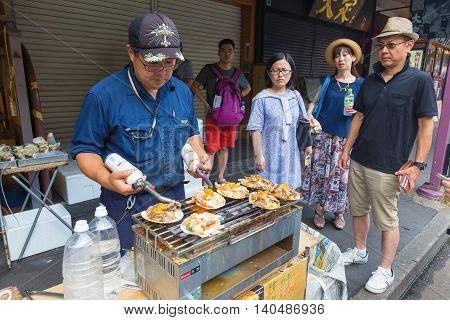 TOKYO JAPAN - 18 JULY 2016 - Jananese man street vendor cooks seafood for his waiting customers at Tsukiji Fish Market in Tokyo Japan on July 18 2016