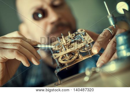 Close up portrait of a watchmaker at work. He is wearing specialist magnifying glass.