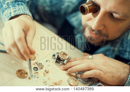 Close up portrait of a watchmaker at work.He is wearing specialist magnifying glass.