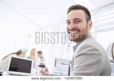 Businessman working on his laptop in the office.Three people mill around them out of focus.