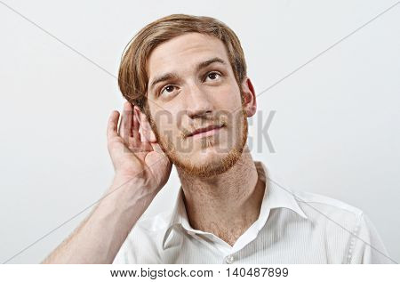 A Young Adult Male Wearing White Shirt with His Hand Near His Ear. Gestures Can Not Hear or Talk Louder.