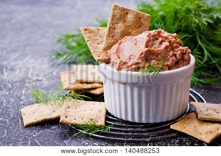 Liver pate with crisps on a dark background. Selective focus.
