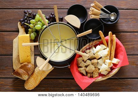 Traditional set of utensils for fondue, with bread, cheese and grapes