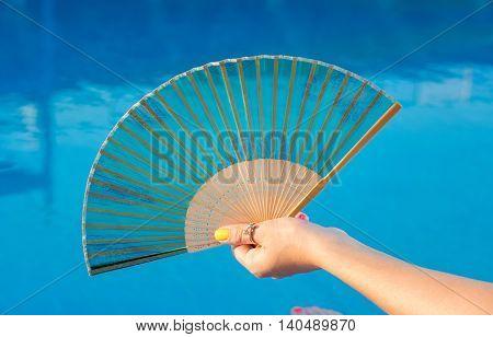 Hand Fan In Girls Hand By The Pool