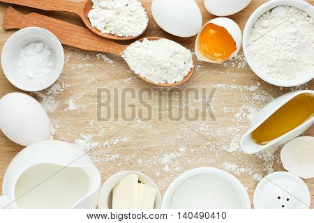 Ingredients for baking - flour eggs salt sugar butter milk. View from above. Rustic background with free text space. Ingredients for the dough. Food background