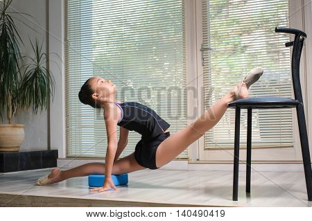 Stretching Little japanese Girl. Attractive beautiful Asian girl doing gymnastics exercises in hall rhythmic gymnastics. Window jalousie in the background. Child sitting on the splits