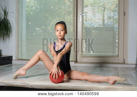 Stretching Little japanese Girl. Attractive beautiful Asian girl doing gymnastics exercises in hall rhythmic gymnastics. Window jalousie in the background. Child sitting on the splits. Red ball in hand.