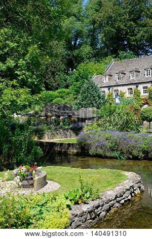 BIBURY, UNITED KINGDOM - JULY 20, 2016 - View across the trout farm garden and River Coln towards The Swan Hotel Bibury Cotswolds Gloucestershire England UK Western Europe, July 20, 2016.