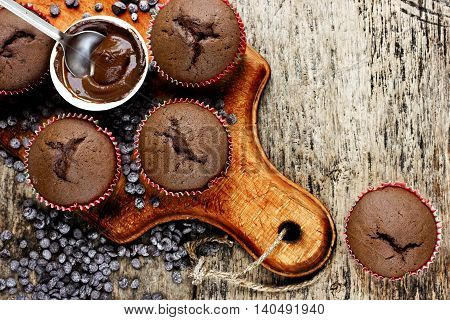 Chocolate muffins and melted chocolate on wooden table with chocolate chips top view blank space for text