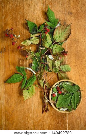 Raspberry. Dried herbs for use in alternative medicine.Herbal medicine phytotherapy medicinal herbs.For preparation of infusions decoctions tinctures powders ointments tea. Background wooden board