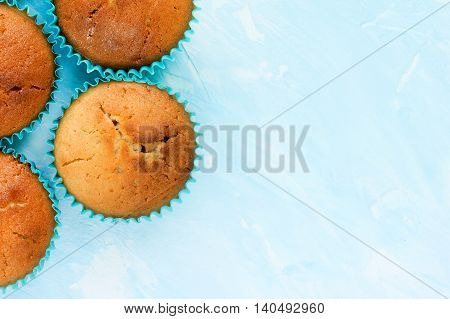 Muffins on blue background blank space for text top view baking background