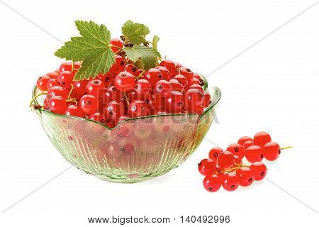 Fresh red currant berries in green glass bowl isolated on white background