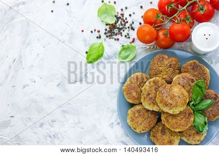 Delicious homemade cutlets with tomatoes and basil on dining table top view blank space for text