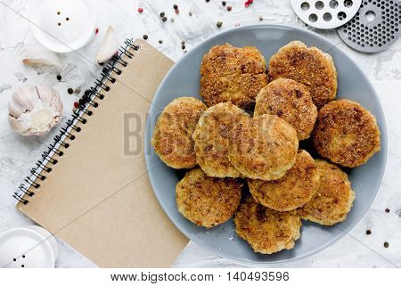 Classic homemade cutlets on white table with notebook top view