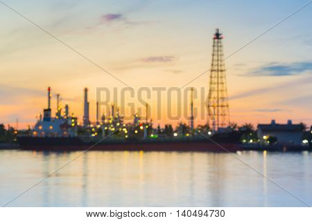 Blurred lights oil refinery river front with sunrise sky background
