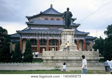 GUANGZHOU / CHINA - CIRCA 1987: People pose for photographs on the statue of Sun Yat Sen, in front of the Sun Yat Sen Memorial Hall in Guangzhou.