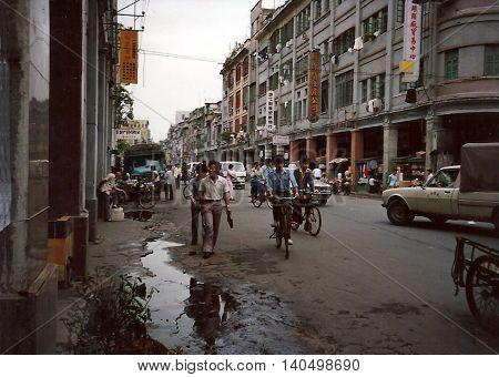 GUANGZHOU / CHINA - CIRCA 1987: People ride bicycles through the streets of Guangzhou on a rainy day.