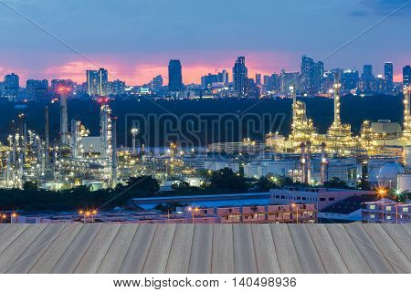 Opening wooden floor, Petrochemical industrial refinery with city background after sunset