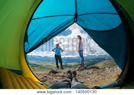 feet in the shoes in a tent and girls on background