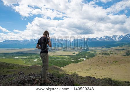 man speaking on the phone in the mountains