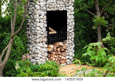 Modern fireplace in the garden landscape with stones and woods