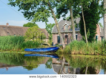 Historic home and a bright blue rowing boat reflected in the mirror like surface of a small river in a small Dutch village. It is a sunny summer day.
