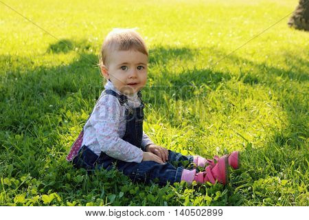 Lovely baby sitting on the green grass in the park and smiling for summer happy days. picnic