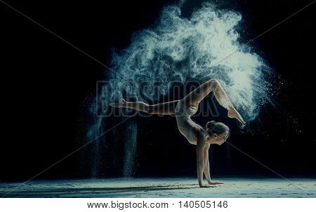 Graceful young woman dancing in cloud of dust