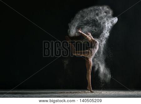 Concept. Flexible woman dancing in cloud of dust