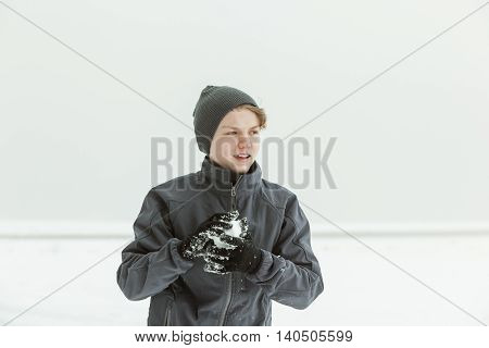 Teen Boy Forming Snowball Outdoors On Winter Day