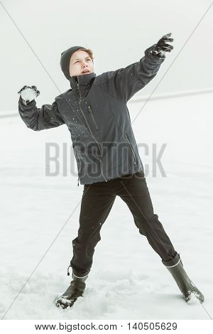 Teenage Boy Throwing Snowball On Winter Day