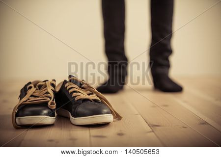 Person Standing Behind Pair Of Shoes On Wood Floor