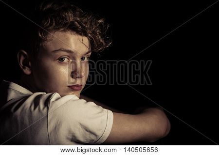 Serious Teenage Boy Looking Back Over Shoulder