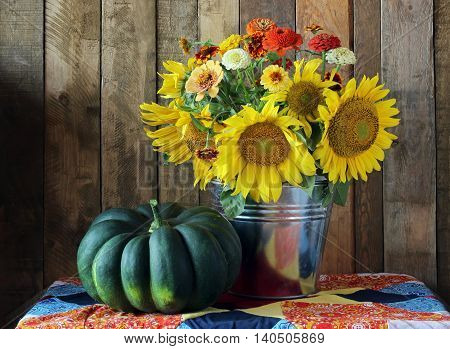 Still life with bouquet of sunflowers and pumpkin in rustic style.