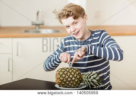 Smiling Teenage Boy Slicing Into Whole Pineapple