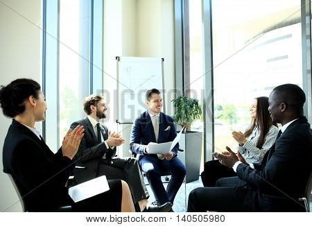 Morning meeting. Group of five young people discussing something while sitting at the table in office together