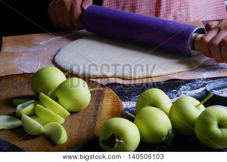 Cooking traditional autumn pie with apples. Cozy kitchen, the girl in a checkered apron unrolls dough.
